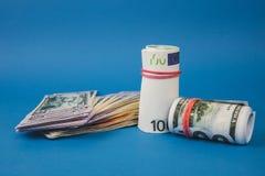 plusieurs bouchons de l'argent de diff?rentes devises sur un fond bleu images stock