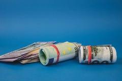 plusieurs bouchons de l'argent de diff?rentes devises sur un fond bleu photos stock