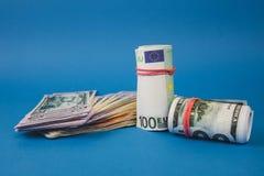 plusieurs bouchons de l'argent de diff?rentes devises sur un fond bleu photographie stock libre de droits