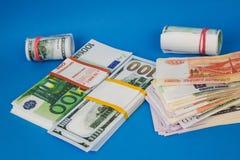 plusieurs bouchons de l'argent de diff?rentes devises sur un fond bleu photo stock