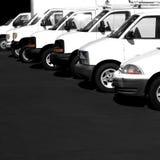 Plusieurs camions de fourgons de voitures ont garé le parking Image stock