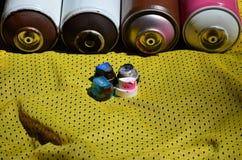 Plusieurs chapeaux pour les pulvérisateurs utilisés de peinture d'aérosol se trouvent sur la chemise de sports d'un joueur de bas Photos libres de droits