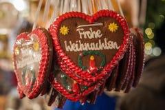 Plusieurs coeurs de pain d'épice avec le Joyeux Noël en allemand au C.A. Photographie stock