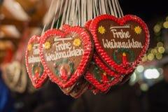 Plusieurs coeurs de pain d'épice avec le Joyeux Noël en allemand au C.A. Image stock