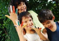 Plusieurs couleurs sur des doigts d'enfants extérieurs Photographie stock