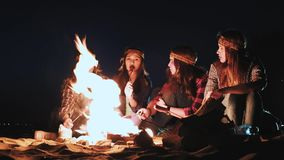 Plusieurs filles s'asseyent par le feu la nuit et font frire des saucisses Discutez et menez la conversation Sont venus sur une c clips vidéos