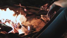 Plusieurs filles s'asseyent par le feu la nuit et font frire des saucisses Discutez et menez la conversation Sont venus sur une c banque de vidéos