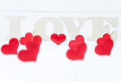 Plusieurs formes de coeur et dans les lettres en bois de fond formant le mot aiment Images stock