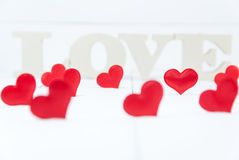 Plusieurs formes de coeur et dans les lettres en bois de fond formant le mot aiment Image stock