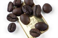 Plusieurs grains de café rôtis sur un lingot de 999 or 9 Photos libres de droits