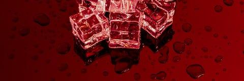 Plusieurs grands glaçons sur un fond rouge de miroir photo stock