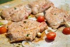 Plusieurs halfs des tomates-cerises sur le gril avec des biftecks de porc Image libre de droits