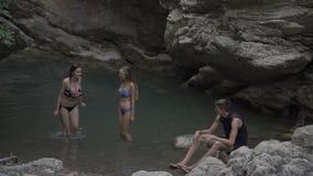 Plusieurs hommes et femmes se baignent dans le lac et la cascade sauvages de montagne Voyage des touristes dans les montagnes et  banque de vidéos