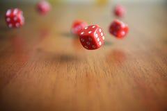 Plusieurs les matrices rouges de roulement tombent sur une table Images libres de droits