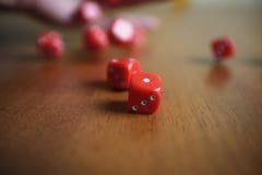 Plusieurs les matrices rouges de roulement tombent sur une table Photos libres de droits
