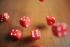 Plusieurs les matrices rouges de roulement tombent sur une table Photos stock
