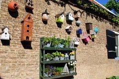 Plusieurs maisons d'oiseau sur un mur de briques Images stock