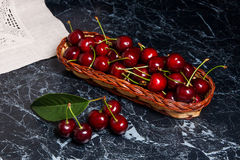 Plusieurs merises rouges et grande feuille verte sur la table Fres Image libre de droits