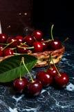Plusieurs merises rouges et grande feuille verte sur la table Fres Photo stock