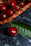 Plusieurs merises rouges et grande feuille verte sur la table Fres Image stock