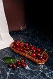 Plusieurs merises rouges et grande feuille verte sur la table Fres Photos stock
