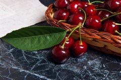 Plusieurs merises rouges et grande feuille verte sur la table Fres Images libres de droits