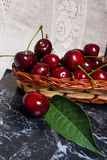 Plusieurs merises rouges et grande feuille verte sur la table Fres Photographie stock