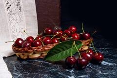 Plusieurs merises rouges et grande feuille verte sur la table Fres Images stock
