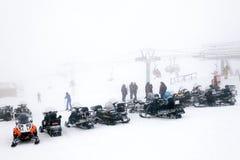 Plusieurs motoneiges se tiennent côte à côte sur le dessus de la montagne dedans photos stock