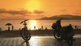 Plusieurs motos se tiennent dans le parking sur le remblai de Nha Trang vietnam Temps et coucher du soleil de soirée banque de vidéos