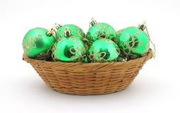 Plusieurs ornements verts de Noël dans le panier Images stock