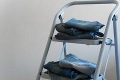Plusieurs paires de jeans sur une échelle photos libres de droits