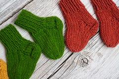 Plusieurs paires de petites chaussettes de laine pour nouveau-né sur la table en bois de cru photographie stock