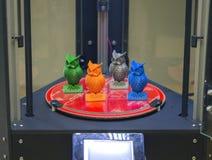 Plusieurs petits hiboux d'objets se tiennent sur la surface de fonctionnement de l'imprimante 3d Photo libre de droits