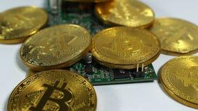 Plusieurs pièces de monnaie des bitcoins et une bande de mémoire électronique sur un fond clair banque de vidéos