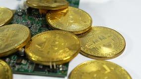 Plusieurs pièces de monnaie des bitcoins et une bande de mémoire électronique sur un fond clair clips vidéos