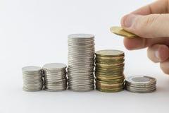 Plusieurs piles des pièces de monnaie avec une main plaçant un Photographie stock