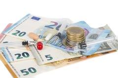 Plusieurs pilules et seringues sur d'euro billets de banque, avec des pièces de monnaie Photo stock