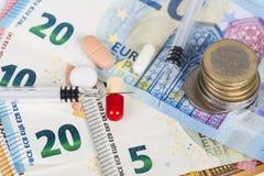 Plusieurs pilules et seringues sur d'euro billets de banque, avec des pièces de monnaie Image stock