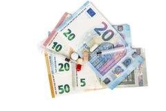 Plusieurs pilules et seringues sur d'euro billets de banque, avec des pièces de monnaie Images libres de droits