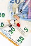 Plusieurs pilules et seringues sur d'euro billets de banque, avec des pièces de monnaie Photographie stock libre de droits