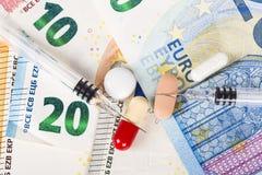 Plusieurs pilules et seringues sur d'euro billets de banque, avec des pièces de monnaie Photos stock
