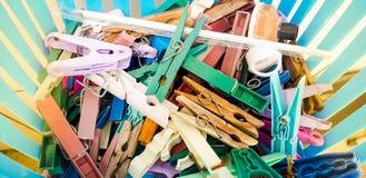 Plusieurs pinces à linge dans une cuvette bleue avec des poutres du soleil à coté photographie stock
