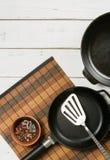 Plusieurs poêles vides de fonte sur un fond en bois blanc poivrons de mélange dans la cuvette Photo stock
