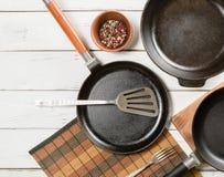 Plusieurs poêles vides de fonte sur un fond en bois blanc poivrons de mélange dans la cuvette Photographie stock libre de droits