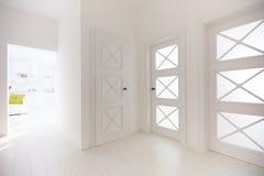 Plusieurs portes en bois avec les insertions en verre décoratives dans le couloir de l'appartement moderne image stock