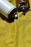 Plusieurs pulvérisateurs utilisés de peinture d'aérosol se trouvent sur la chemise de sports d'un joueur de basket fait en tissu  Images libres de droits