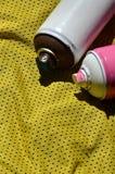 Plusieurs pulvérisateurs utilisés de peinture d'aérosol se trouvent sur la chemise de sports d'un joueur de basket fait en tissu  Photographie stock libre de droits