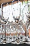 Plusieurs rangées dégagent les verres transparents et propres pour le vin et le champagne sur le compteur préparé pour des boisso photographie stock libre de droits