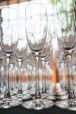 Plusieurs rangées dégagent les verres transparents et propres pour le vin et le champagne sur le compteur préparé pour des boisso images stock